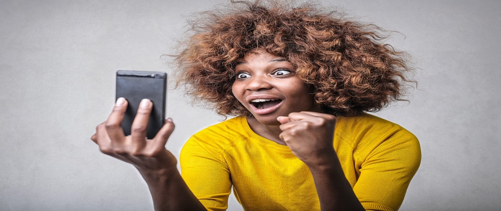 excited lady looking at cell phone